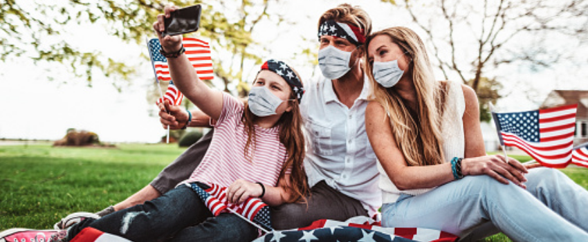 Family wearing masks takes a selfie together outside surrounded by American flags for the Fourth of July