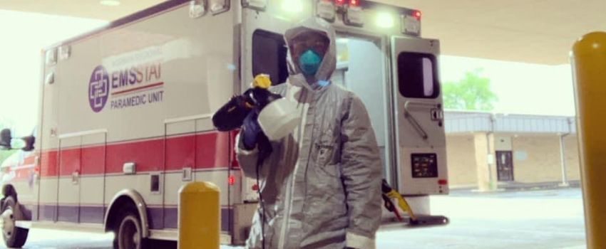 An EMSSTAT paramedic stands in a white hazmat suit holding a paint sprayer in front of an EMSSTAT ambulance.