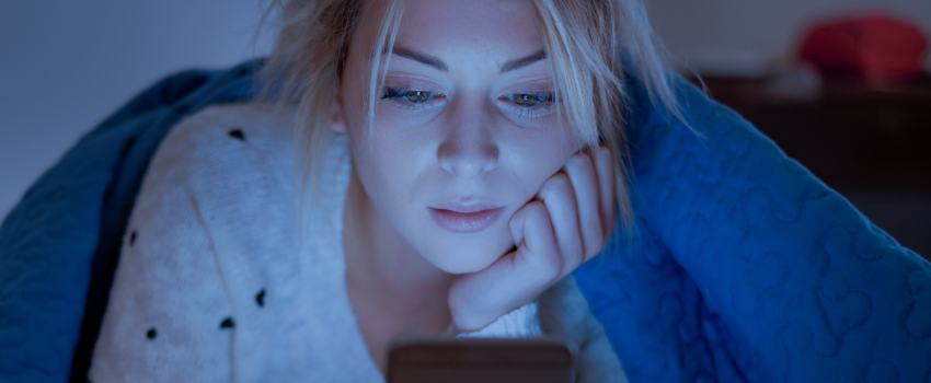 woman looking at cell phone with light on face
