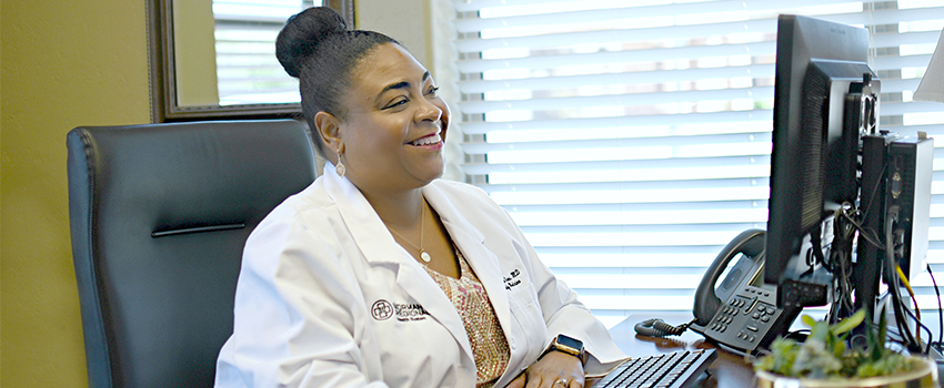 Dr. LaRhonda Sims sits at her desk smiling in her office while completing a virtual visit with a patient.