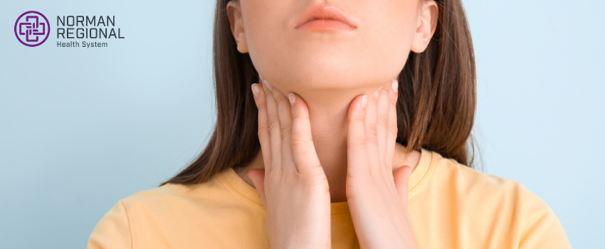 A woman checks her neck for thyroid bulges or protrusions