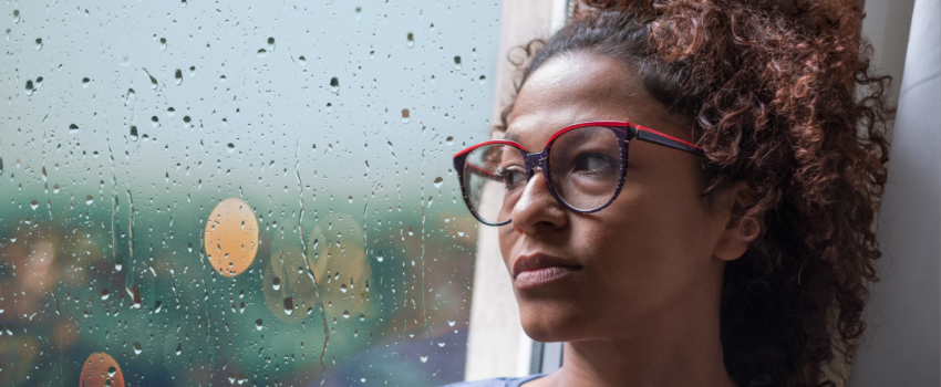 woman leaning on window looking sad