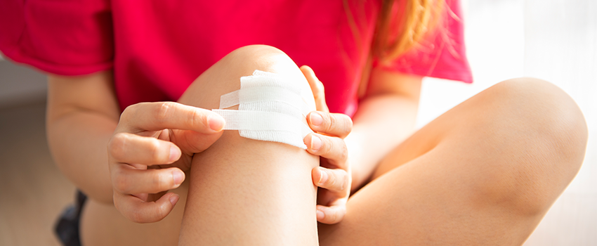 Woman bandaging a wound on her knee.